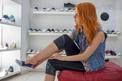 Όμορφο redhead καυκάσιο κορίτσι που επιλέγει και που φορά τα νέα παπούτσια στο κατάστημα Στοκ Εικόνες