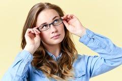 Όμορφο redhead κορίτσι εφήβων με τις φακίδες που φορούν τα γυαλιά ανάγνωσης, χαμογελώντας το πορτρέτο εφήβων στοκ εικόνες