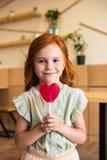 όμορφο redhead κορίτσι που τρώει την καρδιά που διαμορφώνεται lollipop και που κοιτάζει Στοκ φωτογραφία με δικαίωμα ελεύθερης χρήσης
