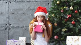 Όμορφο redhead κορίτσι στο κιβώτιο δώρων αγκαλιασμάτων καπέλων Santa απόθεμα βίντεο