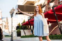 Όμορφο redhead κορίτσι στο φόρεμα που κρατά έναν χάρτη οδηγών πόλεων Στοκ Φωτογραφίες