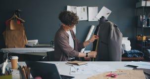 Όμορφο seamstress που μετρά το ένδυμα στις πλαστές πληροφορίες γραψίματος στο σημειωματάριο απόθεμα βίντεο