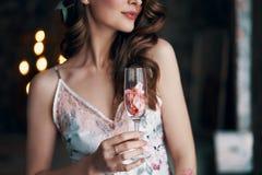 Όμορφο wineglass εκμετάλλευσης γυναικών με τα ροδαλά πέταλα στοκ φωτογραφία με δικαίωμα ελεύθερης χρήσης