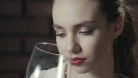 Όμορφο wineglass ρουθουνίσματος γυναικών πορτρέτου και κόκκινο κρασί κατανάλωσης κοντά επάνω απόθεμα βίντεο