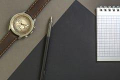 Όμορφων ατόμων wristwatch στο γκρίζο υπόβαθρο Σημειωματάριο και μαύρη μάνδρα στο μαύρο υπόβαθρο στοκ εικόνες