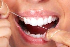 Δόντια γυναικών με το οδοντικό νήμα Στοκ Φωτογραφία