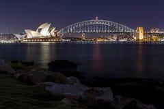 Όπερα του Σίδνεϊ και λιμενική γέφυρα τη νύχτα Στοκ Φωτογραφία