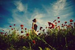 όπιο, γυναίκα ή κορίτσι στον τομέα λουλουδιών του σπόρου παπαρουνών στοκ φωτογραφία