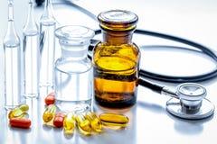 Όργανα και χάπια γιατρών ` s στο ιατρικό σύνολο στο άσπρο backgroun Στοκ φωτογραφία με δικαίωμα ελεύθερης χρήσης