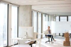 Όργανο ελέγχου υπολογιστών στο γραφείο με τη επιχειρηματία που εργάζεται στο υπόβαθρο στο γραφείο Στοκ Εικόνα