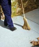 Όχημα αποκομιδής απορριμμάτων στην οδό που σκουπίζει με τα φύλλα φθινοπώρου σκουπών του Στοκ Εικόνες