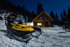 Όχημα για το χιόνι από τα σαλέ σπιτιών στο χειμερινό δάσος με το χιόνι στο ελαφρύ φεγγάρι και τον έναστρο ουρανό Στοκ Φωτογραφία