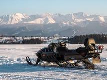Όχημα για το χιόνι και βουνά στο υπόβαθρο Στοκ εικόνα με δικαίωμα ελεύθερης χρήσης