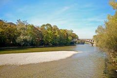 Όχθη ποταμού με τη γέφυρα πέρα από το Isar ποταμό στο Μόναχο, Βαυαρία Γερμανία Στοκ Φωτογραφίες