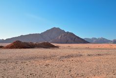 Όχι υψηλά βουνά του κόκκινου ψαμμίτη σε ένα κλίμα της έκτασης ερήμων και ενός μπλε ουρανού αναμμένου από τον ήλιο πρωινού Στοκ Φωτογραφία