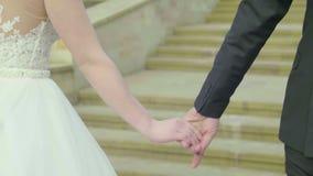 Όψη κινηματογραφήσεων σε πρώτο πλάνο των χεριών εκμετάλλευσης παντρεμένων ζευγαριών Υπαίθριο γαμήλιο βίντεο νυφών και νεόνυμφων φιλμ μικρού μήκους