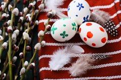 2 όλα τα αυγά Πάσχας έννοιας νεοσσών κάδων ανθίζουν τη χλόη χρωμάτισαν τις τοποθετημένες νεολαίες Χρωματισμένοι αυγά και κλάδοι ι Στοκ Εικόνες