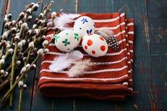 2 όλα τα αυγά Πάσχας έννοιας νεοσσών κάδων ανθίζουν τη χλόη χρωμάτισαν τις τοποθετημένες νεολαίες Χρωματισμένα αυγά στους κλάδους Στοκ Εικόνες