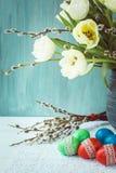 2 όλα τα αυγά Πάσχας έννοιας νεοσσών κάδων ανθίζουν τη χλόη χρωμάτισαν τις τοποθετημένες νεολαίες Λουλούδι άνοιξη και αυγά Πάσχας Στοκ Φωτογραφία