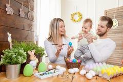 2 όλα τα αυγά Πάσχας έννοιας νεοσσών κάδων ανθίζουν τη χλόη χρωμάτισαν τις τοποθετημένες νεολαίες Ευτυχείς μητέρα και πατέρας που Στοκ Φωτογραφία