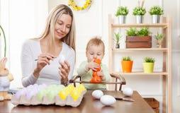 2 όλα τα αυγά Πάσχας έννοιας νεοσσών κάδων ανθίζουν τη χλόη χρωμάτισαν τις τοποθετημένες νεολαίες Ευτυχής μητέρα και το χαριτωμέν Στοκ Φωτογραφίες