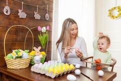 2 όλα τα αυγά Πάσχας έννοιας νεοσσών κάδων ανθίζουν τη χλόη χρωμάτισαν τις τοποθετημένες νεολαίες Ευτυχής μητέρα και το χαριτωμέν Στοκ εικόνα με δικαίωμα ελεύθερης χρήσης