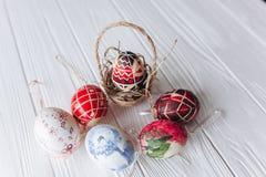 2 όλα τα αυγά Πάσχας έννοιας νεοσσών κάδων ανθίζουν τη χλόη χρωμάτισαν τις τοποθετημένες νεολαίες αυγά σε ένα ξύλινο υπόβαθρο, δι Στοκ Φωτογραφίες