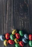 2 όλα τα αυγά Πάσχας έννοιας νεοσσών κάδων ανθίζουν τη χλόη χρωμάτισαν τις τοποθετημένες νεολαίες αυγά σοκολάτας σε ένα ξύλινο υπ Στοκ φωτογραφία με δικαίωμα ελεύθερης χρήσης