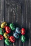 2 όλα τα αυγά Πάσχας έννοιας νεοσσών κάδων ανθίζουν τη χλόη χρωμάτισαν τις τοποθετημένες νεολαίες αυγά σοκολάτας σε ένα ξύλινο υπ Στοκ Φωτογραφία