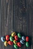2 όλα τα αυγά Πάσχας έννοιας νεοσσών κάδων ανθίζουν τη χλόη χρωμάτισαν τις τοποθετημένες νεολαίες αυγά σοκολάτας σε ένα ξύλινο υπ Στοκ Εικόνα