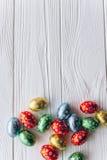 2 όλα τα αυγά Πάσχας έννοιας νεοσσών κάδων ανθίζουν τη χλόη χρωμάτισαν τις τοποθετημένες νεολαίες αυγά σοκολάτας σε ένα ξύλινο υπ Στοκ Εικόνες