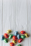 2 όλα τα αυγά Πάσχας έννοιας νεοσσών κάδων ανθίζουν τη χλόη χρωμάτισαν τις τοποθετημένες νεολαίες αυγά σοκολάτας σε ένα ξύλινο υπ Στοκ εικόνες με δικαίωμα ελεύθερης χρήσης
