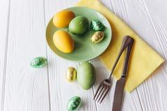 2 όλα τα αυγά Πάσχας έννοιας νεοσσών κάδων ανθίζουν τη χλόη χρωμάτισαν τις τοποθετημένες νεολαίες πιάτο, δίκρανο, αυγά σε ένα άσπ Στοκ φωτογραφία με δικαίωμα ελεύθερης χρήσης