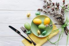 2 όλα τα αυγά Πάσχας έννοιας νεοσσών κάδων ανθίζουν τη χλόη χρωμάτισαν τις τοποθετημένες νεολαίες πιάτο, δίκρανο, αυγά σε ένα άσπ Στοκ φωτογραφίες με δικαίωμα ελεύθερης χρήσης