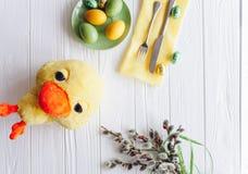 2 όλα τα αυγά Πάσχας έννοιας νεοσσών κάδων ανθίζουν τη χλόη χρωμάτισαν τις τοποθετημένες νεολαίες πιάτο, δίκρανο, αυγά σε ένα άσπ Στοκ Εικόνες