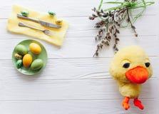 2 όλα τα αυγά Πάσχας έννοιας νεοσσών κάδων ανθίζουν τη χλόη χρωμάτισαν τις τοποθετημένες νεολαίες πιάτο, δίκρανο, αυγά σε ένα άσπ Στοκ εικόνα με δικαίωμα ελεύθερης χρήσης