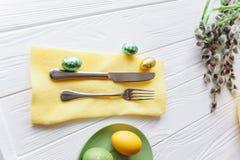 2 όλα τα αυγά Πάσχας έννοιας νεοσσών κάδων ανθίζουν τη χλόη χρωμάτισαν τις τοποθετημένες νεολαίες πιάτο, δίκρανο, αυγά σε ένα άσπ Στοκ Εικόνα