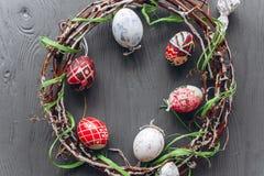 2 όλα τα αυγά Πάσχας έννοιας νεοσσών κάδων ανθίζουν τη χλόη χρωμάτισαν τις τοποθετημένες νεολαίες αυγά και στεφάνι σε ένα ξύλινο  Στοκ Φωτογραφία