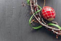 2 όλα τα αυγά Πάσχας έννοιας νεοσσών κάδων ανθίζουν τη χλόη χρωμάτισαν τις τοποθετημένες νεολαίες αυγά και στεφάνι σε ένα ξύλινο  Στοκ Φωτογραφίες