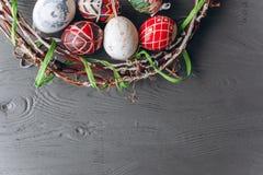 2 όλα τα αυγά Πάσχας έννοιας νεοσσών κάδων ανθίζουν τη χλόη χρωμάτισαν τις τοποθετημένες νεολαίες αυγά και στεφάνι σε ένα ξύλινο  Στοκ εικόνα με δικαίωμα ελεύθερης χρήσης