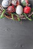 2 όλα τα αυγά Πάσχας έννοιας νεοσσών κάδων ανθίζουν τη χλόη χρωμάτισαν τις τοποθετημένες νεολαίες αυγά και στεφάνι σε ένα ξύλινο  Στοκ Εικόνες