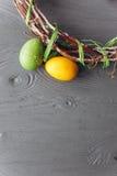 2 όλα τα αυγά Πάσχας έννοιας νεοσσών κάδων ανθίζουν τη χλόη χρωμάτισαν τις τοποθετημένες νεολαίες αυγά και στεφάνι σε ένα ξύλινο  Στοκ Εικόνα