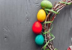 2 όλα τα αυγά Πάσχας έννοιας νεοσσών κάδων ανθίζουν τη χλόη χρωμάτισαν τις τοποθετημένες νεολαίες αυγά και στεφάνι σε ένα ξύλινο  Στοκ φωτογραφία με δικαίωμα ελεύθερης χρήσης