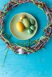 2 όλα τα αυγά Πάσχας έννοιας νεοσσών κάδων ανθίζουν τη χλόη χρωμάτισαν τις τοποθετημένες νεολαίες πιάτο, δίκρανο, αυγά σε ένα άσπ Στοκ εικόνες με δικαίωμα ελεύθερης χρήσης