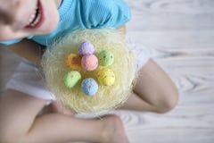 2 όλα τα αυγά Πάσχας έννοιας νεοσσών κάδων ανθίζουν τη χλόη χρωμάτισαν τις τοποθετημένες νεολαίες Ευτυχές χαριτωμένο παιδί που φο Στοκ Φωτογραφίες