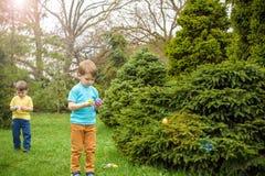 2 όλα τα αυγά Πάσχας έννοιας νεοσσών κάδων ανθίζουν τη χλόη χρωμάτισαν τις τοποθετημένες νεολαίες Ευτυχές χαριτωμένο παιδί που φο Στοκ Εικόνες