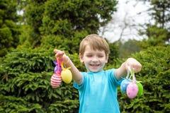 2 όλα τα αυγά Πάσχας έννοιας νεοσσών κάδων ανθίζουν τη χλόη χρωμάτισαν τις τοποθετημένες νεολαίες Ευτυχές χαριτωμένο παιδί που φο Στοκ φωτογραφία με δικαίωμα ελεύθερης χρήσης