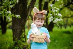 2 όλα τα αυγά Πάσχας έννοιας νεοσσών κάδων ανθίζουν τη χλόη χρωμάτισαν τις τοποθετημένες νεολαίες Ευτυχές χαριτωμένο παιδί που φο Στοκ Εικόνα