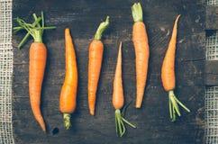 Όλος-φυσικά καρότα που παρατάσσονται στον ξύλινο πίνακα Στοκ Εικόνες