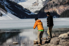 δύο άτομα που βλέπουν το Lake Louise και τα βουνά Στοκ φωτογραφία με δικαίωμα ελεύθερης χρήσης